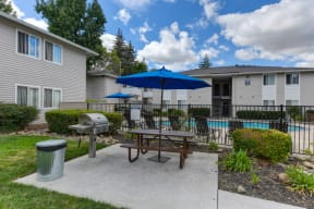 BBQ Picnic Area with View of Swimming Pool with Grill, Picnic Table and Trashcan