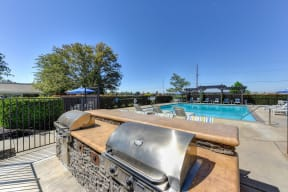 BBQ Picnic Area with Grills and View of Lounge Chairs and Pool