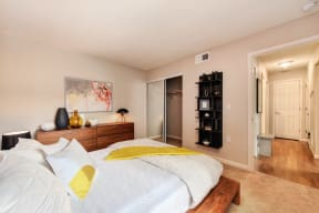Red Wall Bedroom with Full Sized Mattress and Wooden Frame, White Comforter and Yellow Blanket, Wood Dresser,