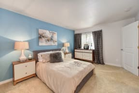 Bedroom with Large Window, Carpet, Blue Wall, Brown/White Dresser, Lamp and Gray Curtains