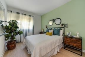 Model home bedroom with light mint green accent wall. Room has queen sized bed and two nightstands on each side of the bed.