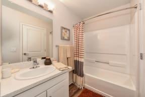 Community Bathroom and Vanity, Hardwood Inspired Floor and Bathtub