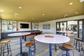 Community Clubhouse Game Room with Round Desk, Stools, Chess Set, Mounted Flatscreen Television
