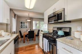 Dining Room/Kitchen with Wood Inspired Floor, Rug, Oven, Stove with Blue Tea Kettle, Microwave, Wood Dining Room Table and Chairs,