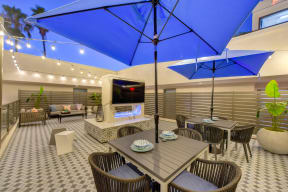Outdoor rooftop lounge area at dusk.  There are bright blur patio umbrellas with tables, chairs and fireplace with flat screen TV above.