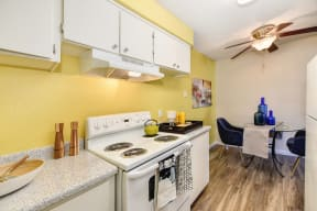 Kitchen and Dining Area with Bright Yellow Accent Walls, Hardwood Inspired Floors, Stove and White Cabinets
