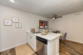 Kitchen with Dishwasher, Hardwood Inspired Floor, White Cabinets and View of Dining Area