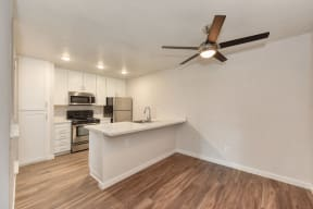 Kitchen with Wood Inspired Floors, Ceiling Fan/Light, Refrigerator, and White Counter