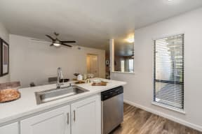 Kitchen with View of Dining Area, Hardwood Inspired Floor, Dishwasher, Ceiling Fan/Light and Window
