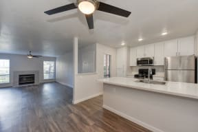Kitchen with Wood Inspired Floors, Ceiling Fan/Light, Refrigerator, View of Living Room andWhite Counter