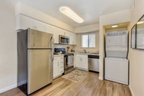 Kitchen with Washer/Dryer , Hardwood Inspired Floor, Refrigerator and White Cabinets