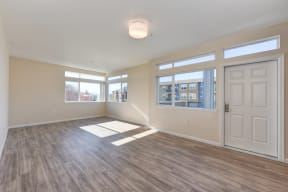 Large Living Room with Wood Inspired Floors, Large White Door, and Open Window