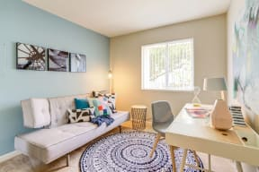 Bedroom with a futon against the baby blue accent wall and a work from home desk on the opposite wall.
