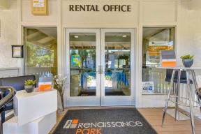 Rental office entrance with two glass doors.  Tables outside the doors and a Renaissance Park door mat outside the doors.
