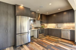 Leasing Office Kitchen with Hardwood Inspired Floors and Stainless Steel Refrigerator, Wood Inspired Floor, Wood Cupboards, Oven, Stove, Microwave