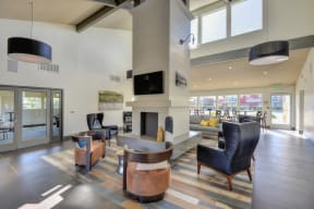 Leasing Office with Gray Sofa and Chairs, Wood Inspired Floors, Mounted Flat Screen Television,Exit Sign above Glass Door