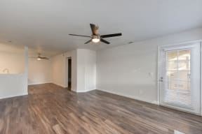 Living Room with Ceiling Fan,  Wood Inspired Floor and White Walls