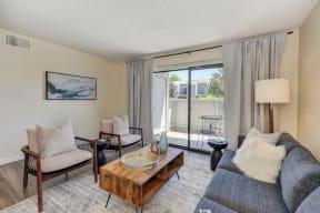 Living with Sliding Patio Doors,  Hardwood Inspired Floor, Gray/White Rug, Gray Sofa and Round Mirror
