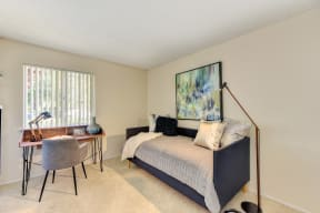 Bedroom with daybed and desk.  Desk is positioned in front if the bedroom window.