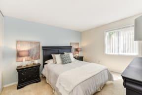 Bedroom with Carpet, Black Headboard, Window and Bedside Dresser