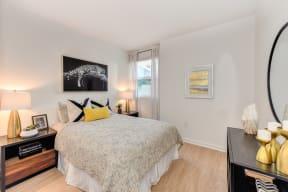 Bedroom with Hardwood Inspired Floors, White Comforter Mattress, Windows and Black Dresser