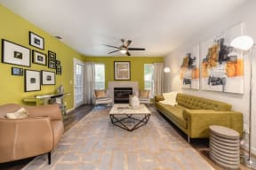 Living Room with Wood Inspired Floor, Ceiling Fan/Lights, Green Sofa, White Chairs and Framed Photos on Wall