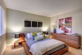 Large Bedroom with Full Sized Bed on Elevated Wood Frame, Carpet, Wood Dressers, Small Black Lamps on each side of Bed, Abstract Painting on Wall
