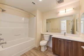 Master Bathroom with Wood Inspired Floor, Toilet, Bathtub, Full Vanity