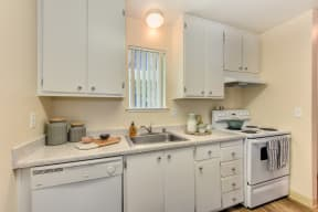 Kitchen with white cabinets and appliances, including dishwasher and stove/oven.