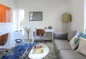 Study Lounge Area with Blue/Gray Carpet, Wood Back Swivle Chairs, Gray Sofa, White Tables, Printer and Window