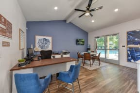 Office Entry with Hardwood Inspired Floor, Ceiling Fan/Light, Desks, Blue Chairs and View of Pool