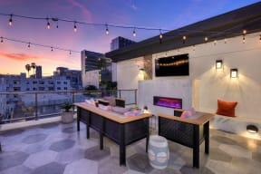 Roof top lounge area at sunset.  The sky is a beautiful blue and orange color. Lounge area comes with couches, chairs, fire pit and flat screen TV on wall.