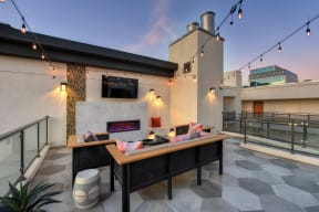 Community rooftop lounge area at dusk.  Area is equipped with chairs, couches, flat screen TV mounted on the wall and views of the city