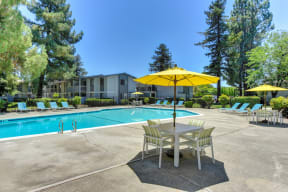 Swimming Pool with Lounge Seating and Tables. Tables have bright yellow umbrellas for shade.