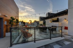 Rooftop lounge area at sunset. Lounge has chairs and couches with fire pit and TV