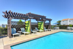 Swimming Pool Cabanas with Lounge Chairs, Lime Green Curtain and Blue Patio Umbrella in the Distance