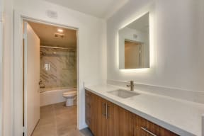 Vacant bathroom with white quartz counters and custom tiled tub/shower area