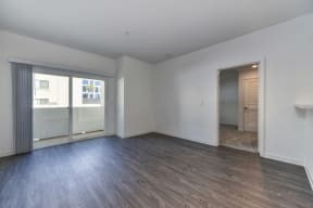 Vacant apartment living room with views of the sliding glass door to the patio. Home has hardwood inspired flooring through out and views of the bedroom.