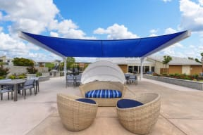 Outdoor Lounge with Wicker Chair, Blue Sun Cover, Tables and Chairs, Blue Sky with Clouds