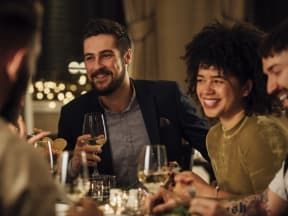a group of young adults enjoying dinner