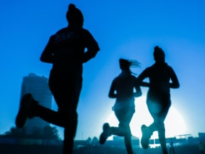 Silhouette of three runners on a city trail with a high rise building in teh background