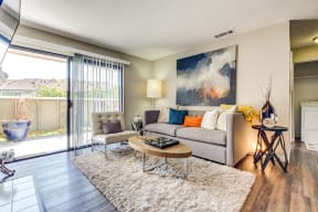 Pittsburg CA Apartments - Open Space Living Room with Stylish Interiors and Hardwood Floor Featuring Sliding Door to Patio