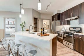 Chandler Apartments-The Core Chandler Designer Kitchen with Large Island, Modern Light Fixtures, and Matching Stainless Steel Appliances