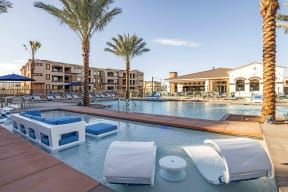 Apartments in Chandler AZ-The Core Chandler Resort-Style Swimming Pool Surrounded by Lounge Chairs, Palm Trees, and a Separate In-Water Seating Area