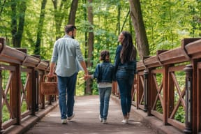 family walking in the woods across the bridge at Windsor Ridge, Austin, TX, 78727