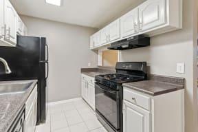 Model kitchen showcasing black appliances and tiled floor