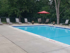 Rectangle pool with brown lawn chairs and table with red umbrella in corner
