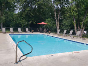 Rectangle pool with brown lawn chaairs, table with 4 chairs and red umbrella in back corner