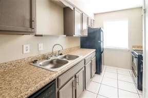 Kitchen with tile flooring. Brown cabinets, brown countertops, black appliances and a stainless steal sink.