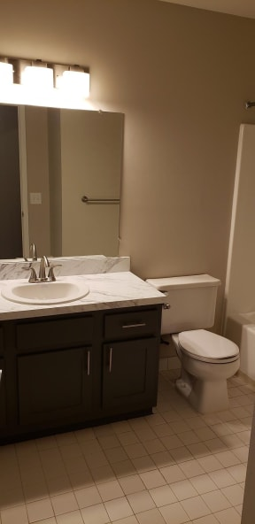 Bathroom with grey cabinets, white and grey countertops, and a larger mirror.